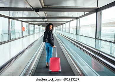 woman in the moving walkway at the airport with a pink suitcase.