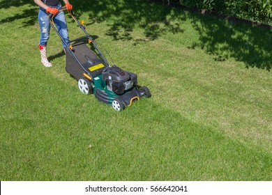 Woman mowing with lawn mower in the garden, gardening concept