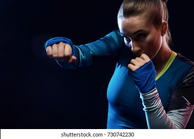 Woman muay thai boxer fighting. Fit young female boxer in sportswear isolated on black background