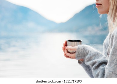 Woman with mug of coffee by winter sea, blue mountains. Cozy picnic with thermos of hot steamy beverage tea on beach. Girl is enjoying nature, life, relaxation, Christmas mood.