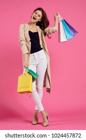 woman with multi-colored packages on a pink background, shopping