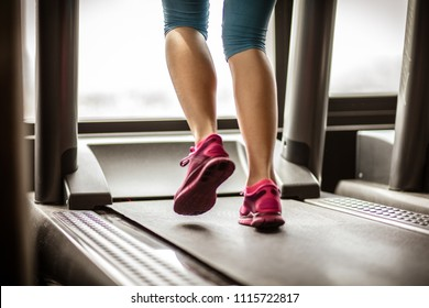 Woman muscular feet in sneakers running on the treadmill.