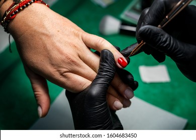 Woman in a nail salon receiving a manicure by a beauty technician