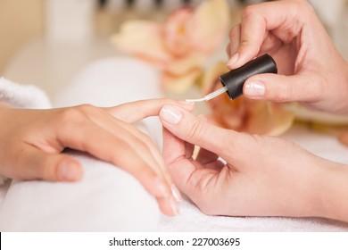 Frau im Nagelsalon, die Maniküre von Kosmetikerinnen erhält. Nahaufnahme von weiblicher Hand, die auf weißem Handtuch ruht