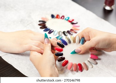 Woman at nail studio chosing color of nail polish
