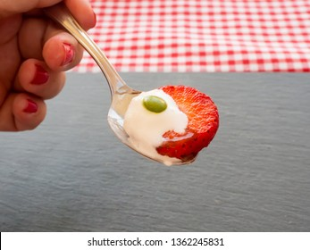 A woman with nails painted red with a spoon in his hand with cream, a chocolate color and a strawberry piece