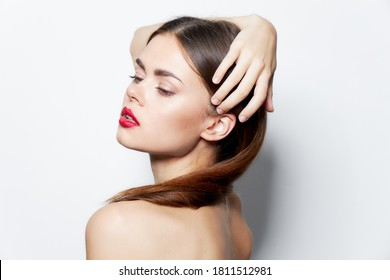 Woman naked shoulders attractive look red lips holds hand on head natural look