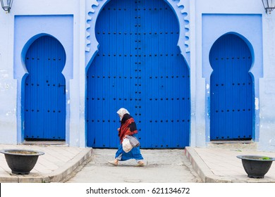 Woman in national dress jellaba walking down the street past arches in traditional Moroccan style. Chefchaouen or Chaouen is known that the houses in this city are painted in blue. Morocco. April 2016