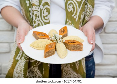 Woman in national kalagayi holding plate with shekerbura and pakhlava in hand