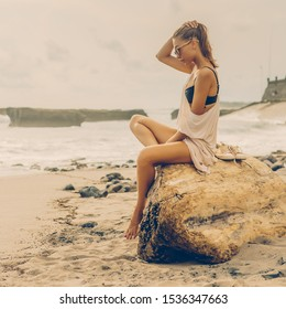 Woman natural beauty. Beautiful girl sit on big stone. Young lady on exotic sand beach at sea coast enjoying sunset or ocean sunrise. Travel, surfer relax and active yoga meditating lifestyle concept.