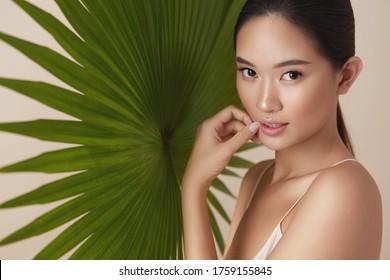 Frau. Natürliche Schönheit auf hellem Hintergrund. Asiatisches Modell-Touchface und Blick auf Kamera gegen tropische Pflanze. Weiblich mit AktMake-up, glatter, Hydratisierung und glühender Haut.