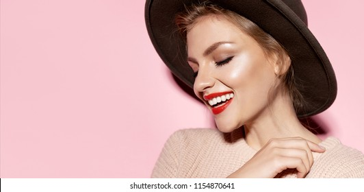 Woman with natural makeup looking away and smiling on pink background. Youth and skincare concept