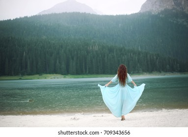 Woman in Nature. Back view of Beautiful brunette in blowing dress by Black lake at  national park Durmitor in Montenegro.
