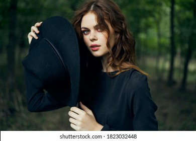 Woman in nature black suit hat fantasy magic