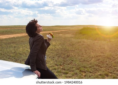 A woman in nature, with her head thrown back, enjoys a meal.