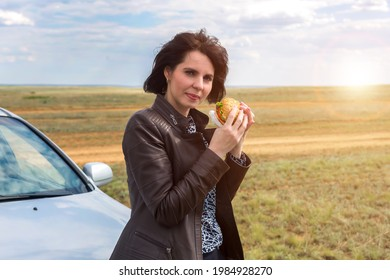 A woman in nature with her head thrown back enjoys a meal.