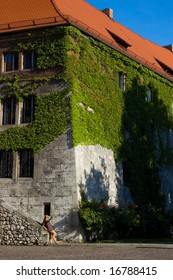 Woman near ancient house in the ivy