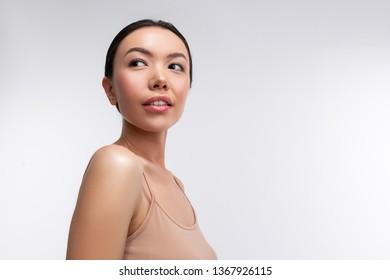 Woman near background. Dark-eyed beautiful woman wearing beige camisole standing near white background