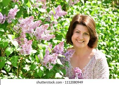 woman near blooming lilac.