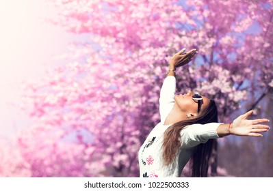 Woman near the blossoming spring tree, free happy  enjoying freshness and beauty of nature. Freedom concept.