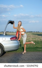 Woman near the car, with her baggage