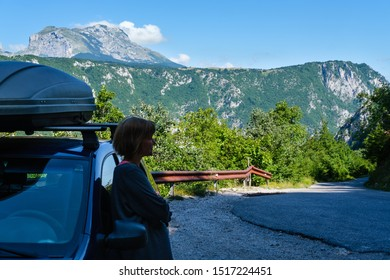 Woman near car (unrecognizable) on secondary countryside road through mountain Durmitor National Park, Montenegro, Europe. Focus on background (foreground, woman, is not in focus).