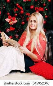 Woman near Christmas tree reads a book