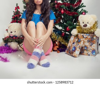 Woman near her gift and christmas tree at background in studio