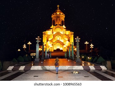 Woman near The Holy Trinity Cathedral or Tsminda Sameba Church at night in Tbilisi, Georgia
