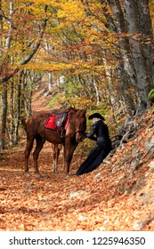 Woman near the horse in the autumn forest