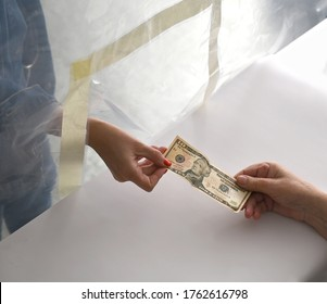 Woman near plastic barrier pays dollars cash at the checkout. COVID-19 pandemic