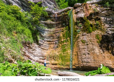 Woman near waterfall in mountain of Caucasus. Summer landscape with waterfall and woman in forest of Caucasus mountain.