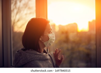 Woman near window at sunset in isolation at home for virus outbreak. Stay home concept.