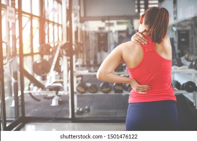Woman with neck and back pain, massage of female body, ache in woman's body in the gym background. Healthcare and exercise concepts.