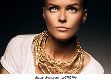 woman with necklace of gold rope in white shirt