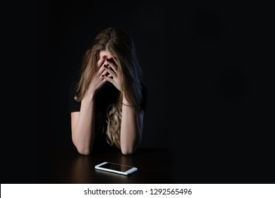 Woman with negative surprised face looking something in smartphone. Sad teenager with mobile phone, scared of threatening,