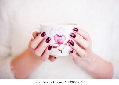 woman neils manicure with a cup of coffee