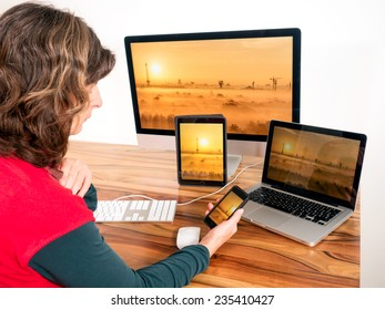 Woman with networked computers and mobile devices