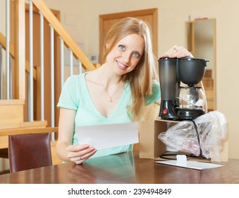 Woman with new electric coffee maker at home