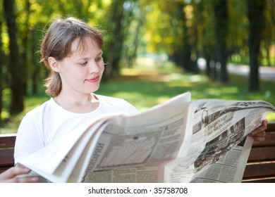 woman with newspaper in park