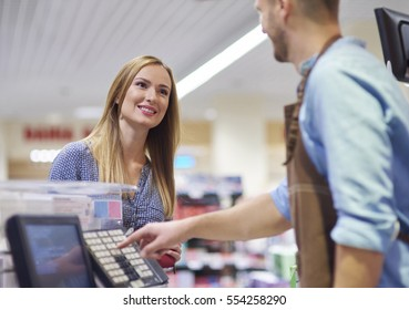 Woman next to cash register talking with sales clerk