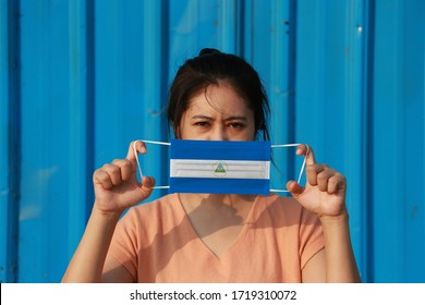 A woman with Nicaragua flag on hygienic mask in her hand and lifted up the front face on blue background. Tiny Particle or virus corona or Covid 19 protection. Concept of Combating illness.