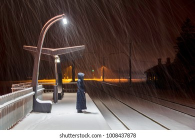The woman at night station is waiting the train