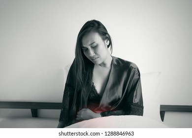 The woman in nightwear suffering from abdominal pain in the bedroom, Stomachache