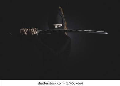 Woman ninja cosplay with katana at the dark background
