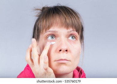 Woman with no make-up applying cosmetic cream under her eyes