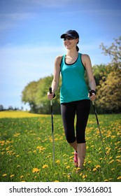 a woman nordic walking through the fields at the springtime
