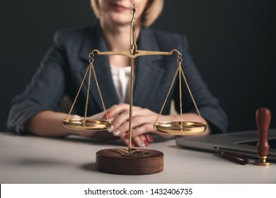 Woman with notary books in office. Wooden gavel with libra and laptop concept.