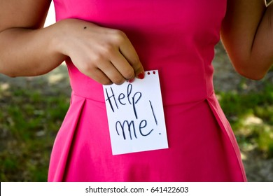 Woman with a note in her hands with the words help me