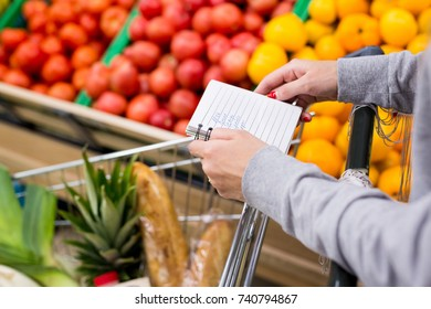 Woman with notebook in grocery store choosing vegetables, holding shopping list.